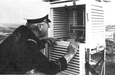 1982. Coastguard George Hall reading thermometers inside Stevenson Screen